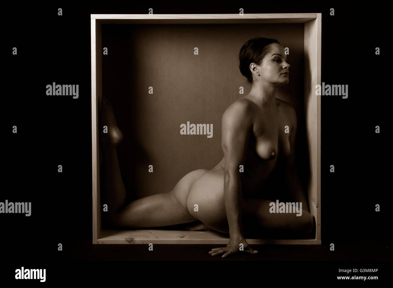 Mujer desnuda estiramiento en la casilla Foto de stock