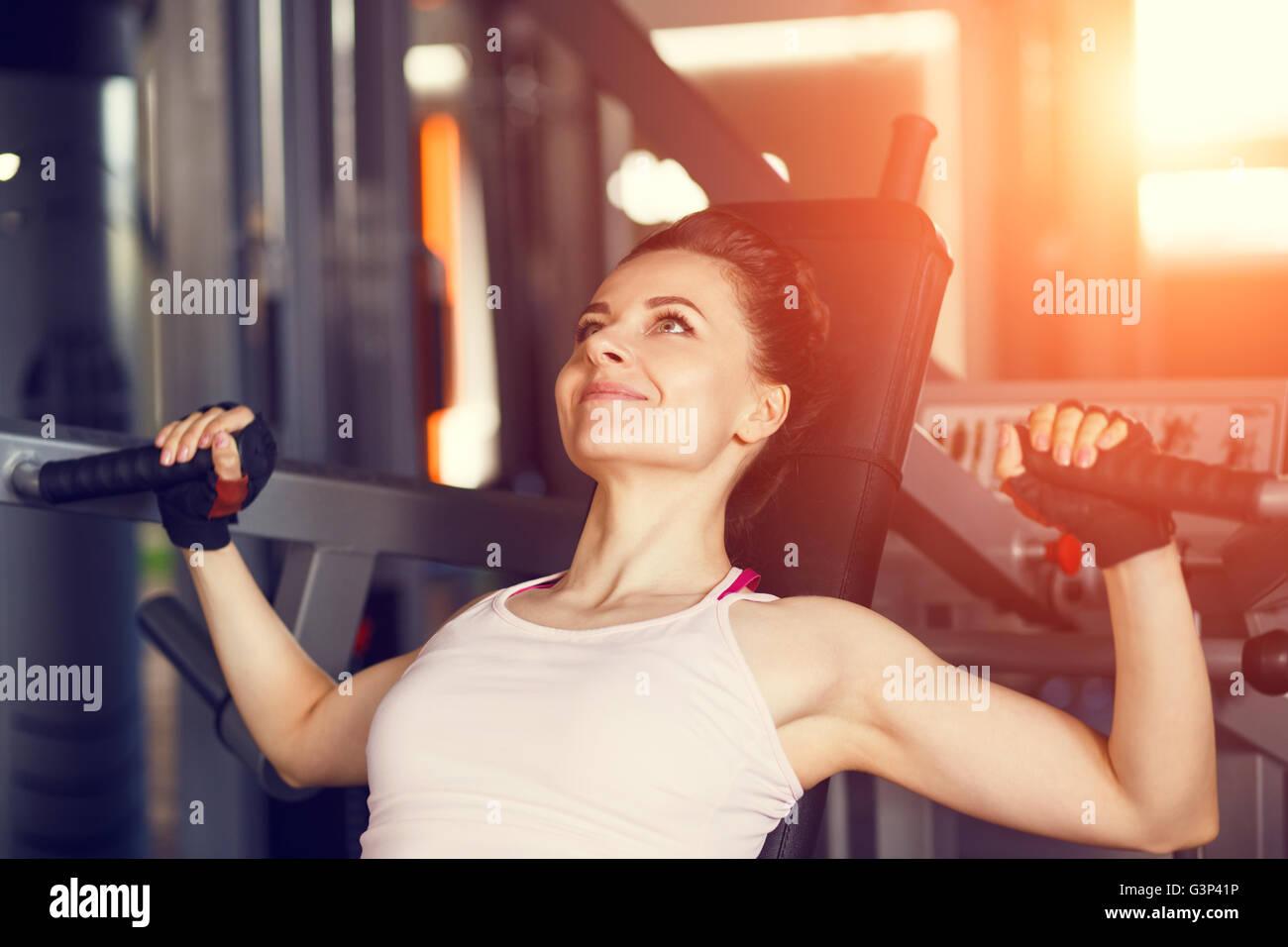 Mujer sonriente joven haciendo ejercicio en el gimnasio pecho volar la máquina. Imagen De Stock