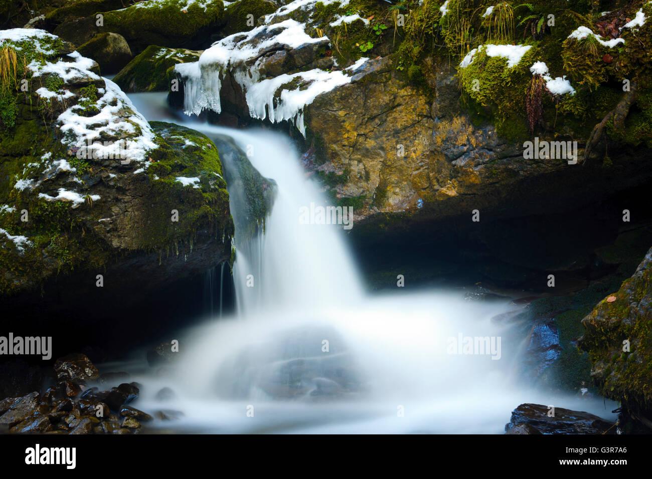 Pequeña cascada durante el invierno con el desenfoque de movimiento, Haute Savoie, Francia. Foto de stock