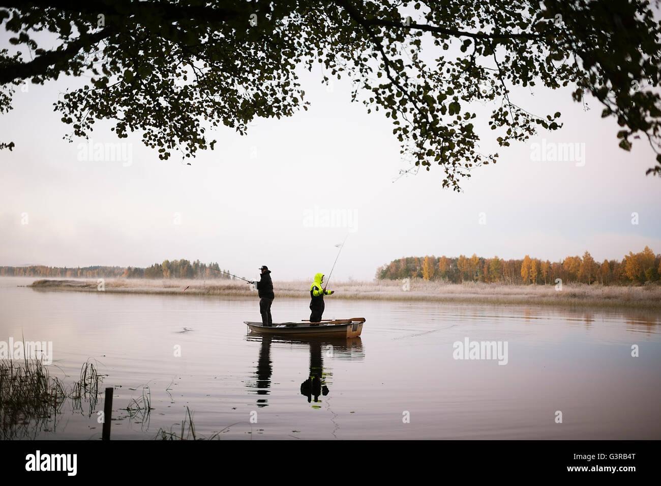 Suecia, Vastmanland, Bergslagen, Torrvarpen de hombres jóvenes, la pesca en el lago al atardecer Imagen De Stock