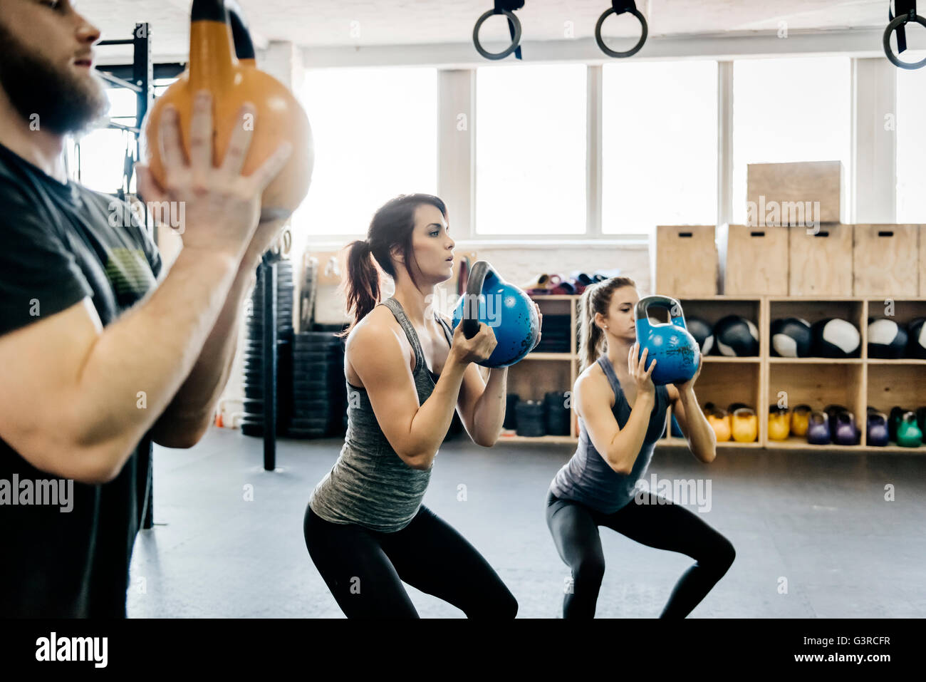 Alemania, hombre y mujeres jóvenes un entrenamiento con kettlebells en gimnasio Foto de stock