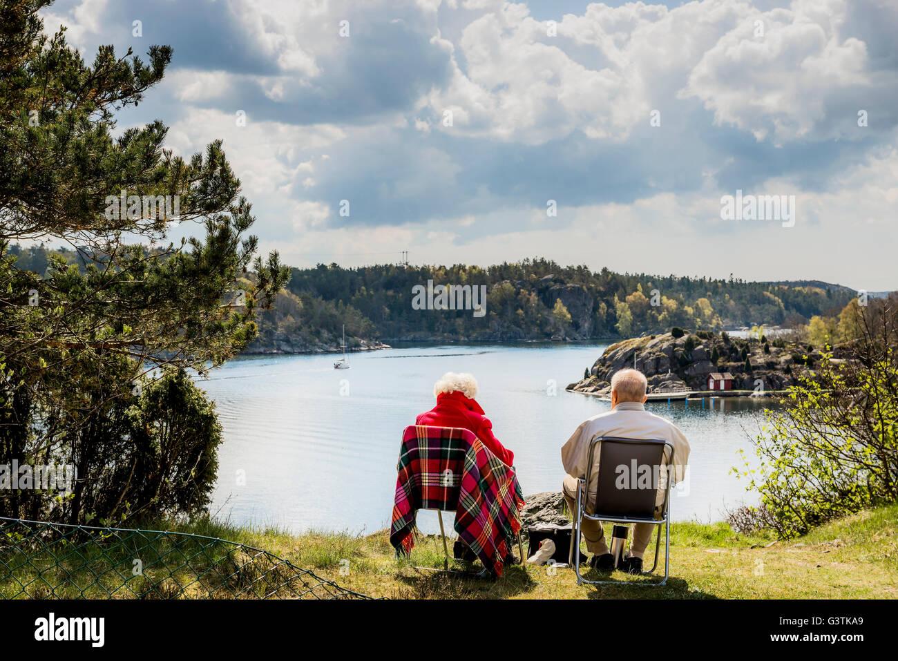Suecia, Costa oeste, Bohuslan, parejas ancianas sentadas en sillas y mirando a ver Imagen De Stock