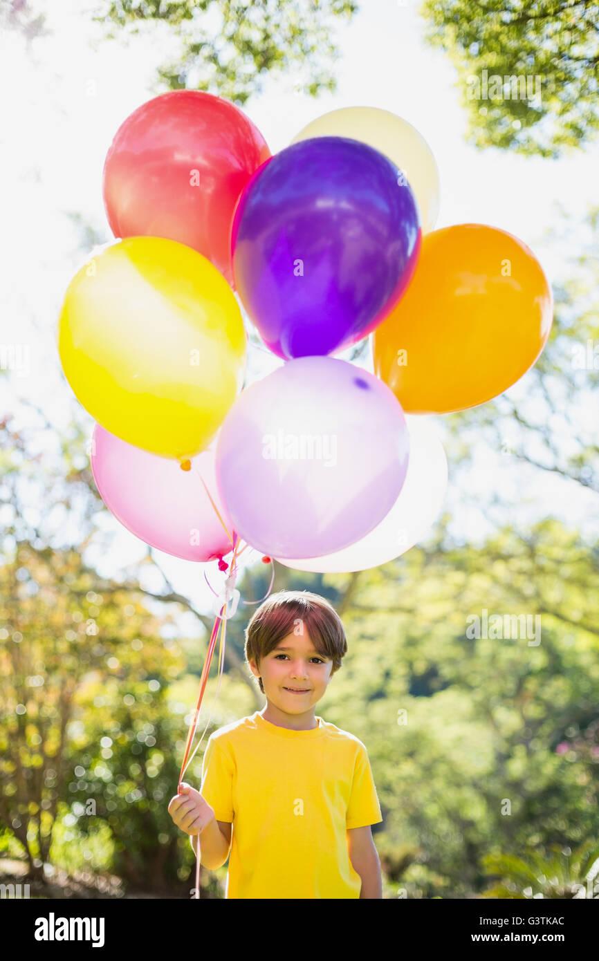 Retrato de niño sonriente sosteniendo globos en park Imagen De Stock