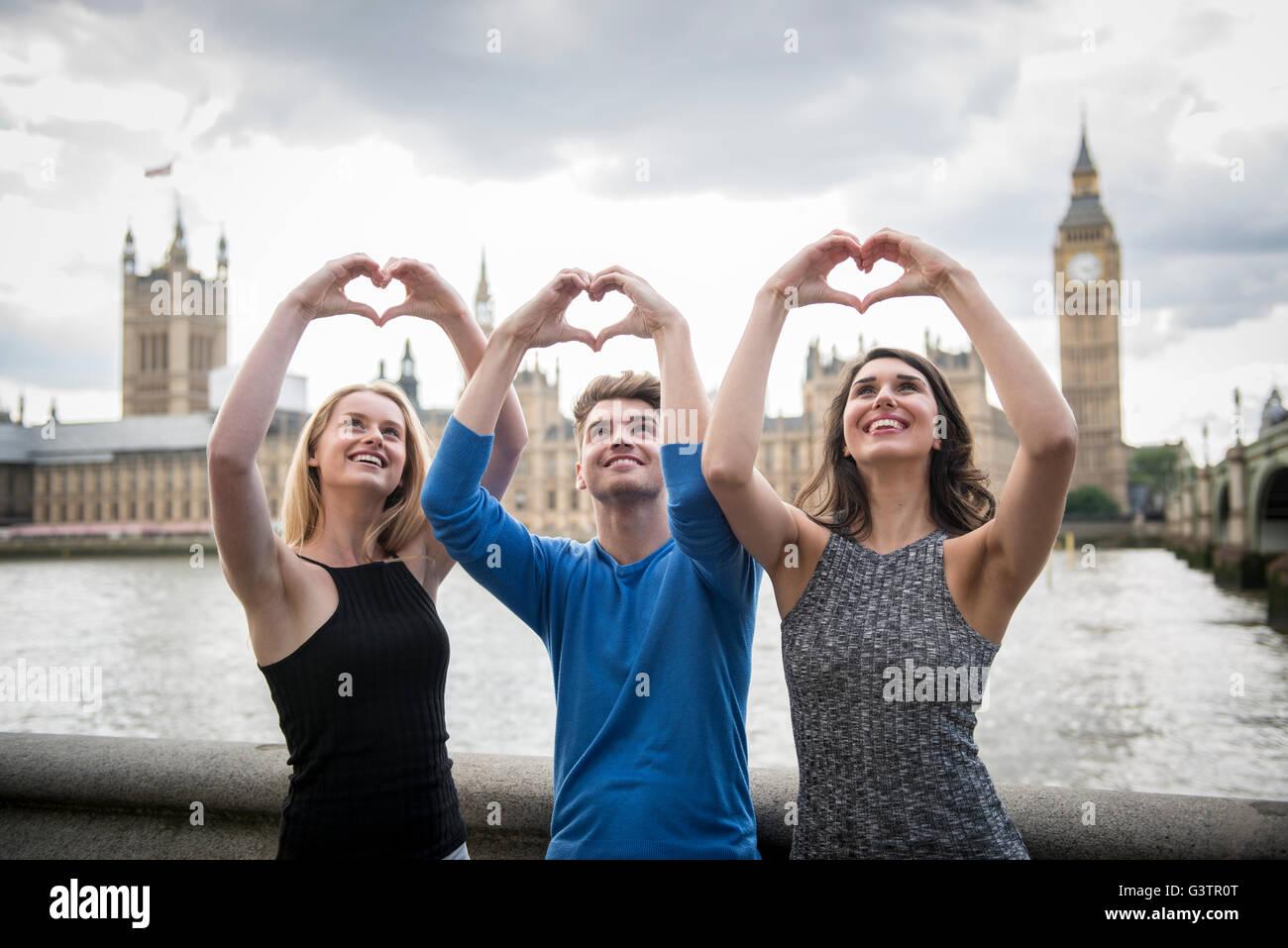 Tres amigos hacen una forma de corazón con sus manos con las Casas del Parlamento en el fondo. Imagen De Stock