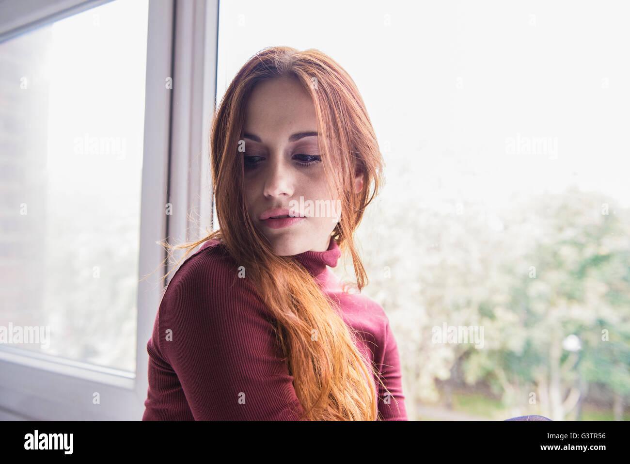 Retrato de un atractivo joven sentado junto a una ventana. Imagen De Stock
