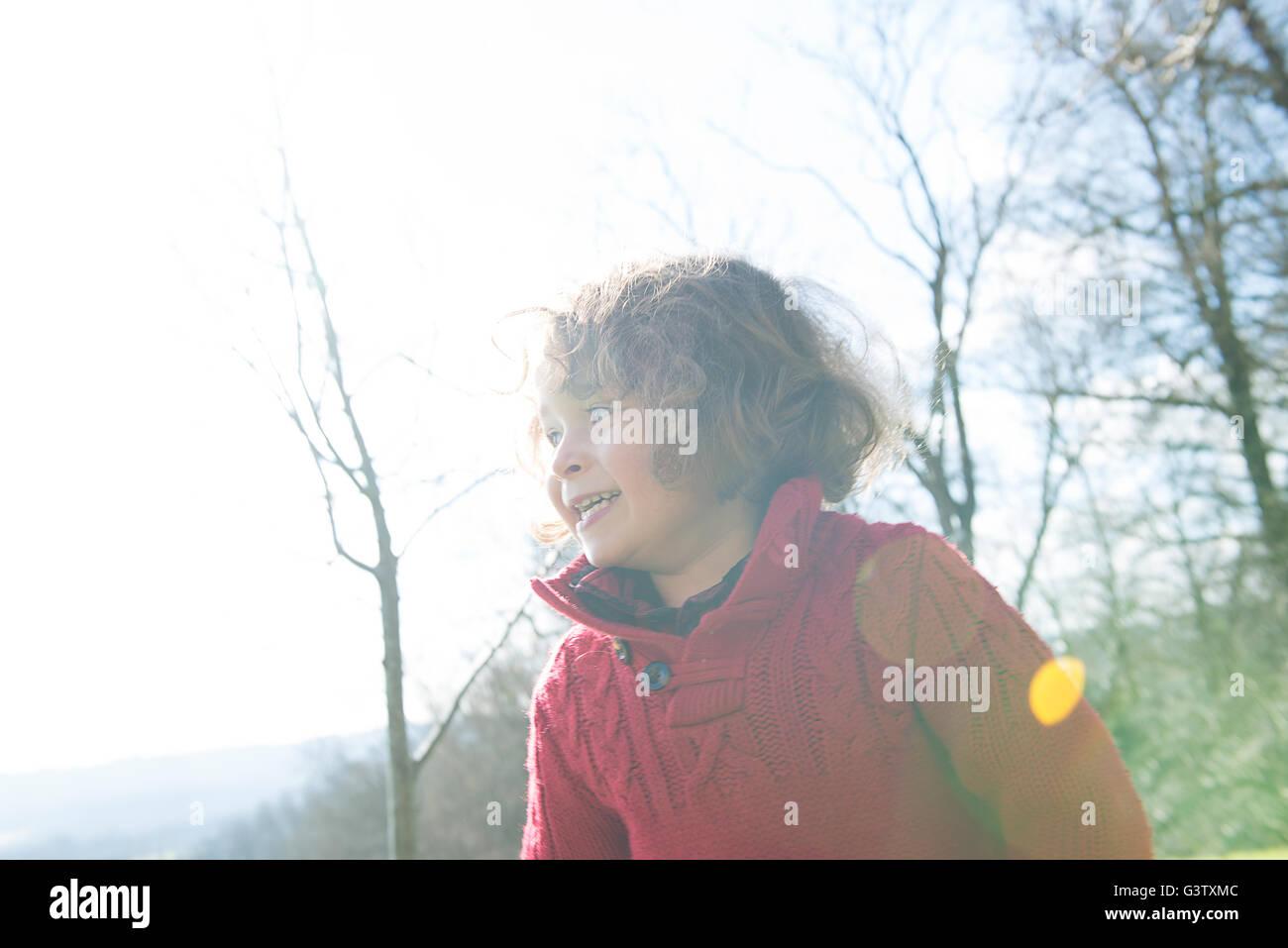 Un niño de cuatro años en un puente rojo de pie en el sol en un jardín. Imagen De Stock