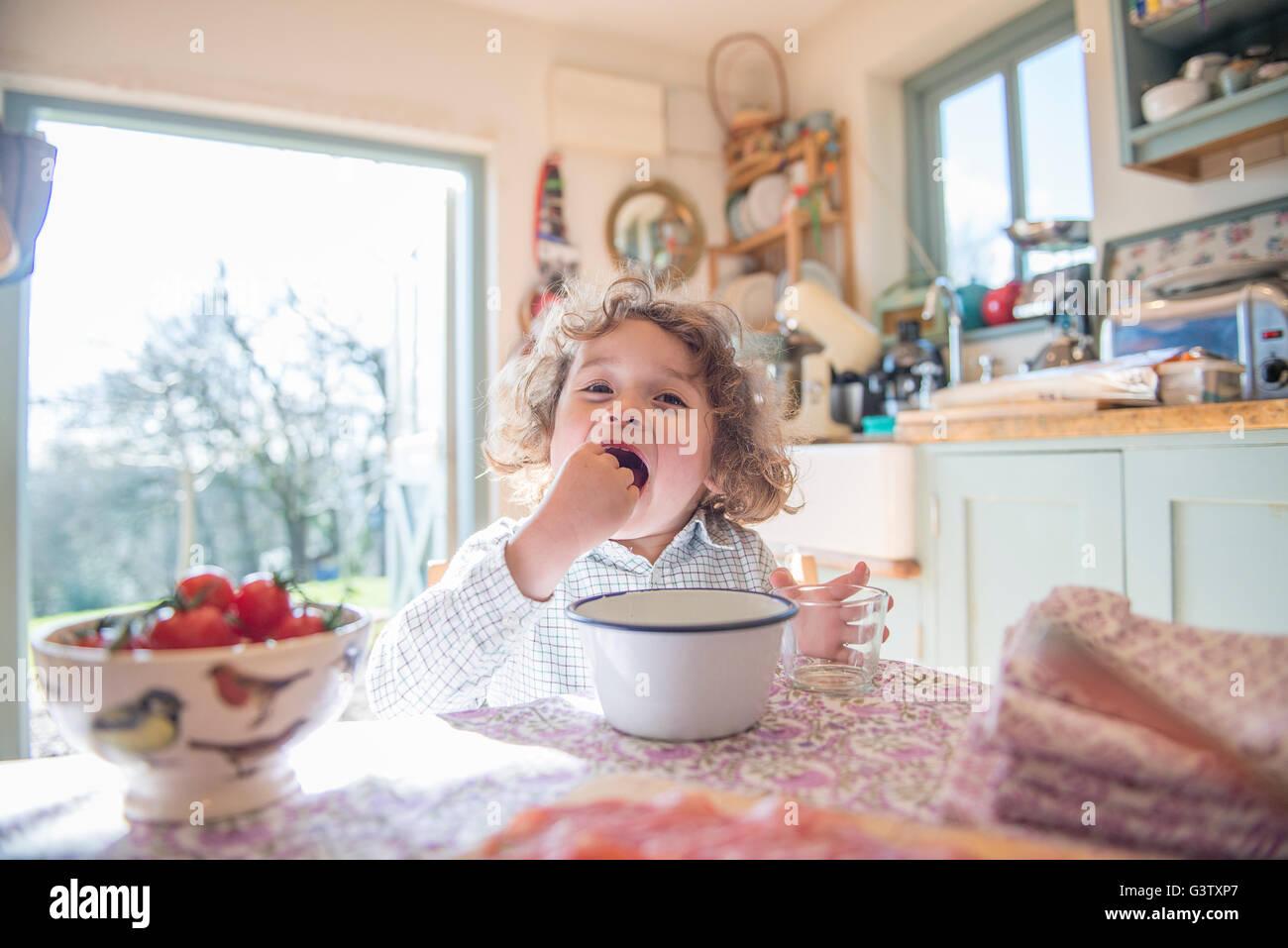Un niño de cuatro años de edad sentado en una mesa comiendo su almuerzo. Foto de stock