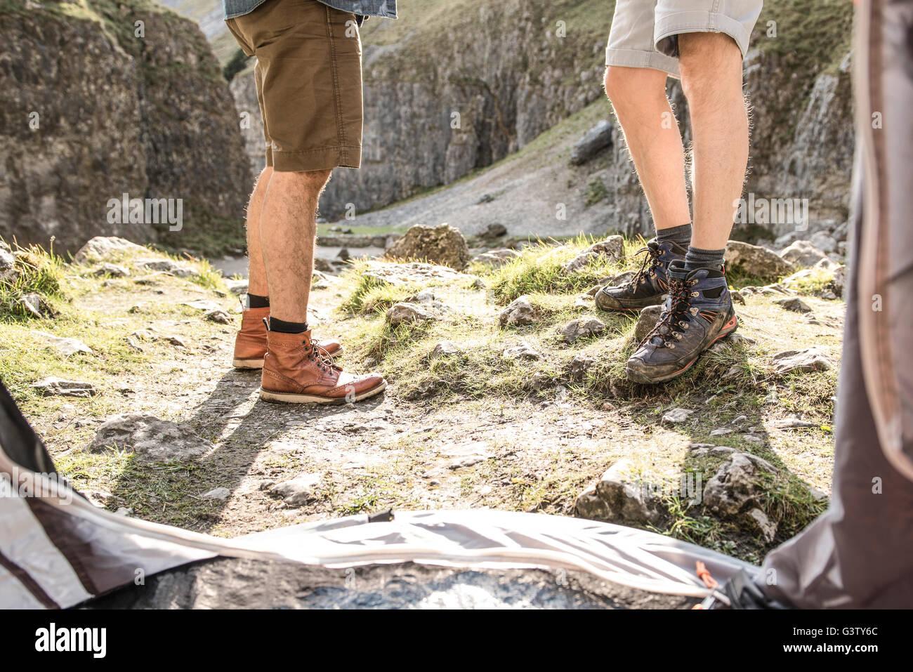 Las piernas de dos hombres vistos desde el interior de la carpa en un terreno escarpado. Imagen De Stock
