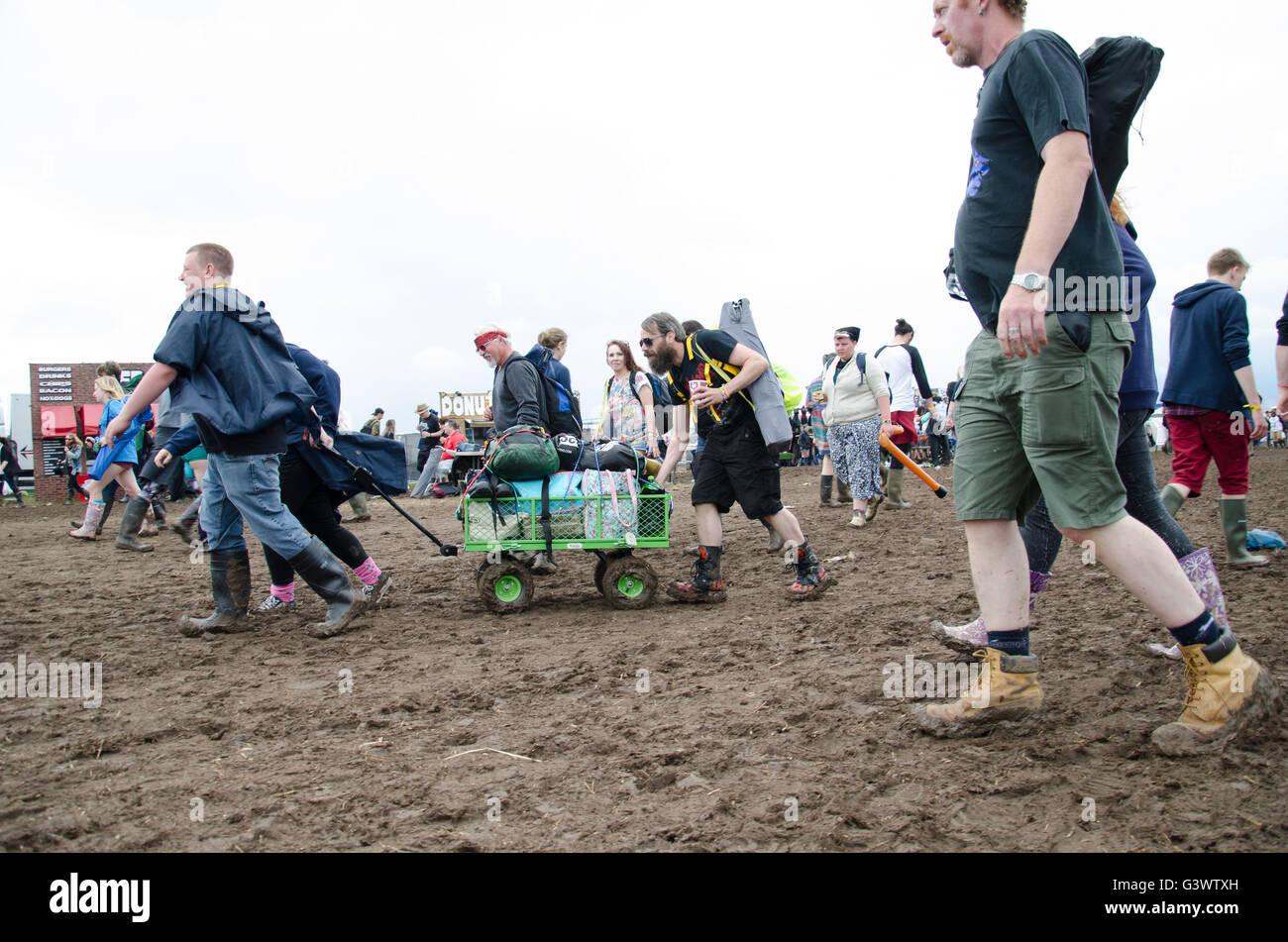 Los fans llegan a descargar tirando de camiones de equipo para acampar en el lodo profundo después de las tormentas Imagen De Stock
