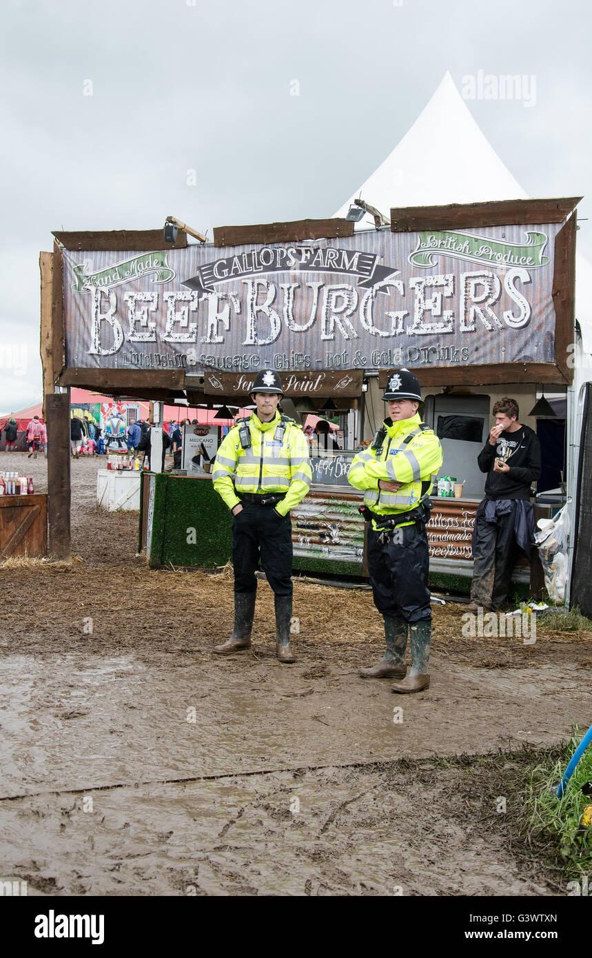 Descargar cops de pie en el barro con botas Wellington delante de beefburger stand en descargar music festival Donington Imagen De Stock