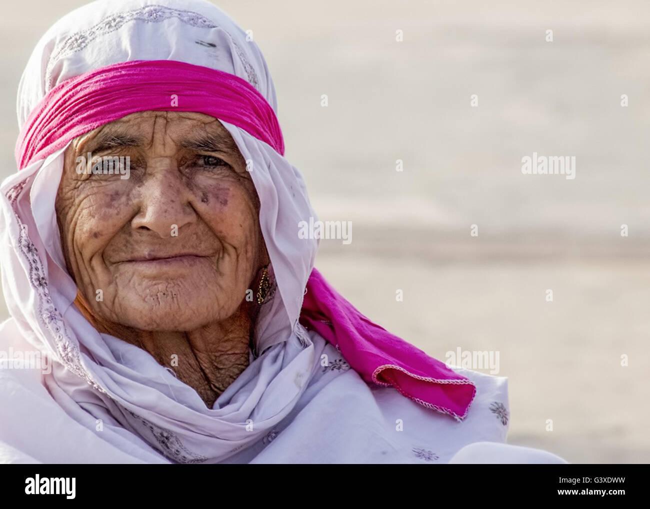 Ancianos árabe mujer vistiendo una túnica blanca y roja, bufanda, banda de cabeza. Foto de stock