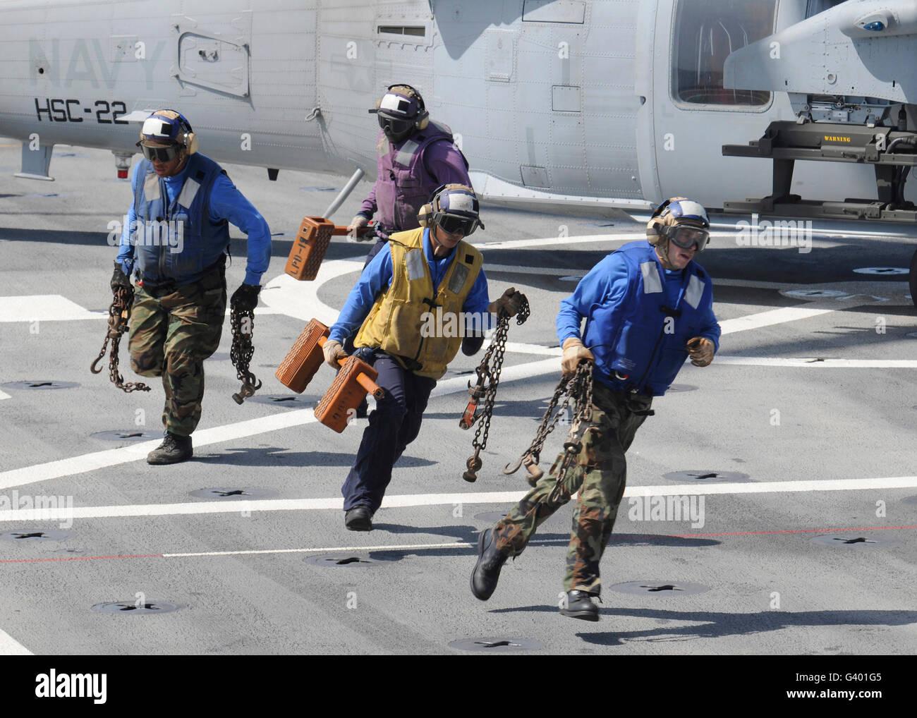 Retirar los calzos de marineros y cadenas de un MH-60 Sea Hawk helicóptero. Imagen De Stock