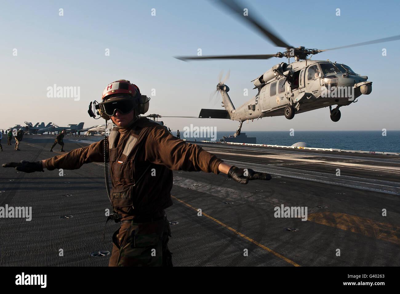 Aviador busca una cubierta clara como un MH-60S Sea Hawk despega el USS John C. Stennis. Imagen De Stock