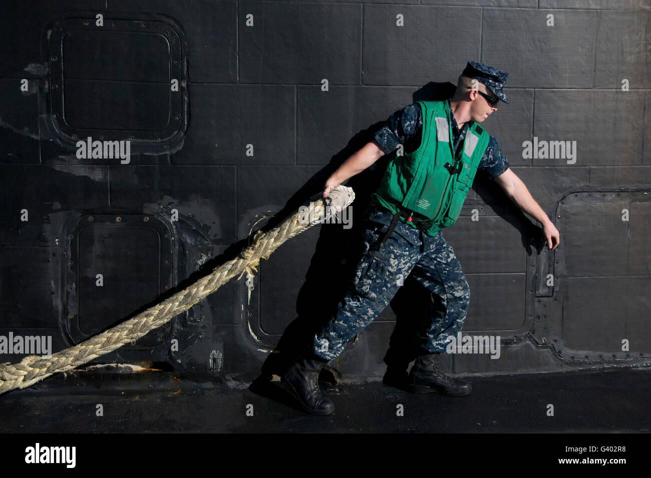 Técnico de control de incendios lances una línea gruesa del puerto desde el remolcador. Imagen De Stock