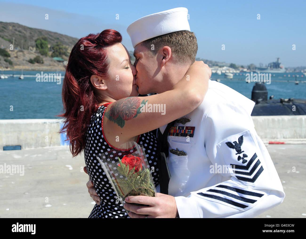 Marina marinero besa a su esposa durante el regreso a casa. Imagen De Stock