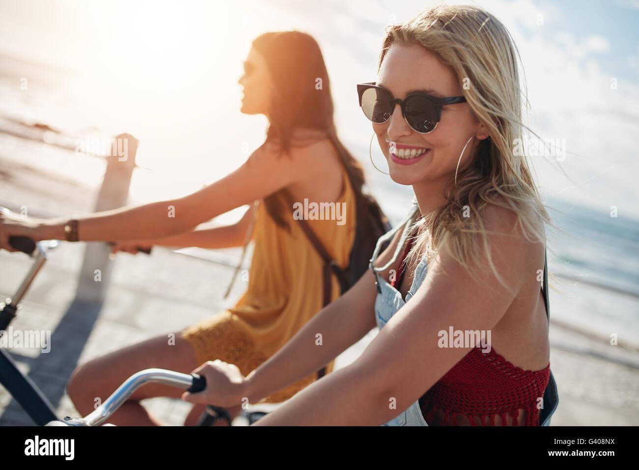 Mujer sonriente montando bicicleta con su amiga en un día soleado. Dos amigas en bicicleta por un paseo marítimo. Imagen De Stock