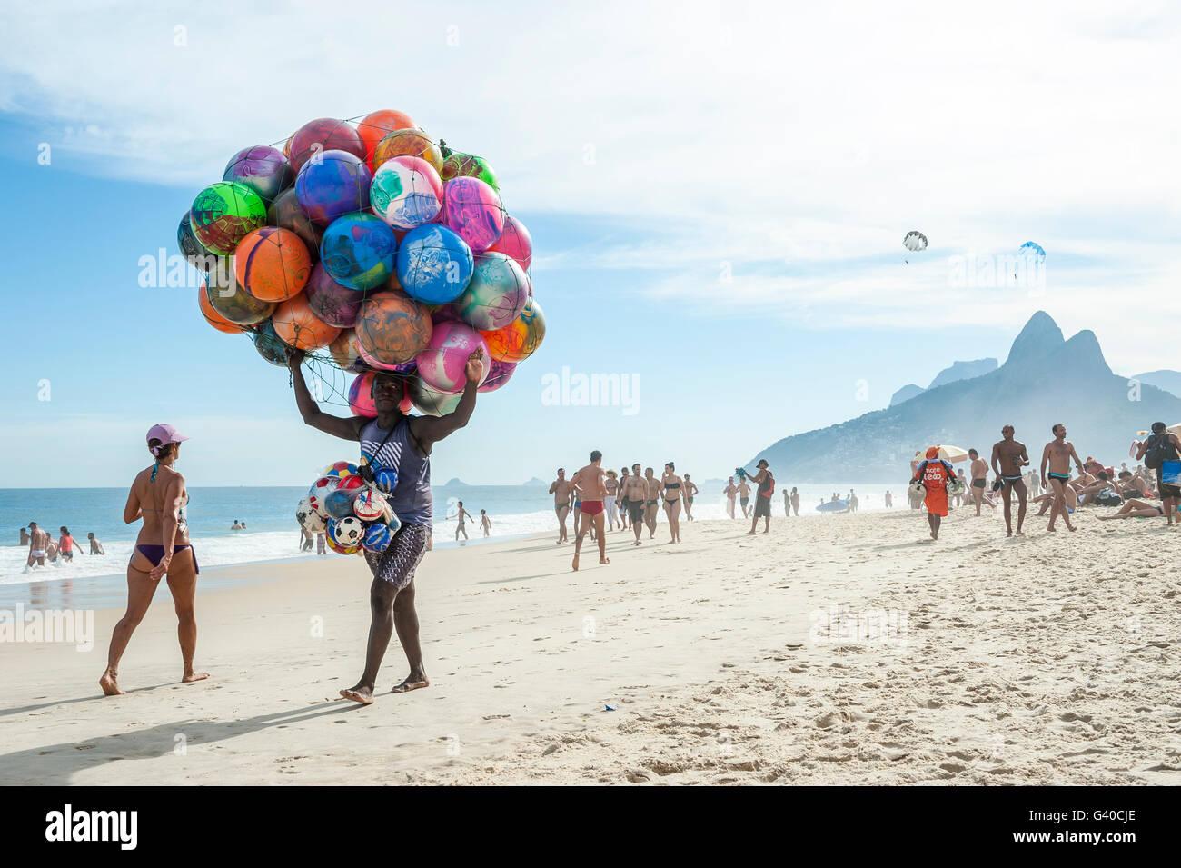RIO DE JANEIRO - 20 de enero de 2013: Playa proveedor de colorida balones de playa lleva su mercancía a lo Imagen De Stock
