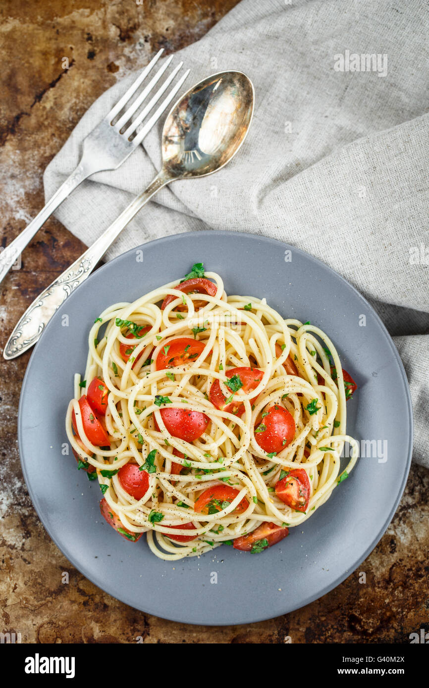 Espaguetis pasta con tomates cherry y perejil en el fondo rustric Imagen De Stock