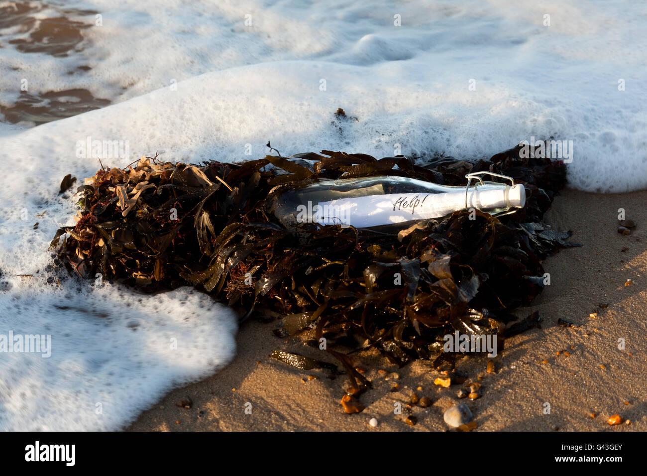 Mensaje es una botella lavada 'Ayuda' en la playa Foto de stock