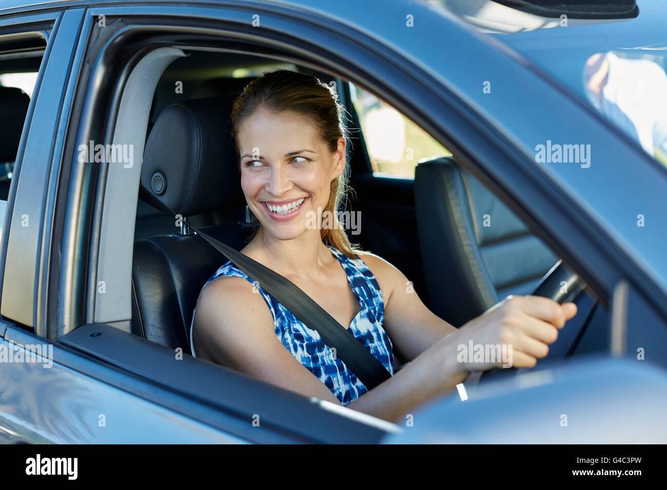 Modelo liberado. Mujer joven mirando a través de la ventana de coche, sonriendo. Imagen De Stock