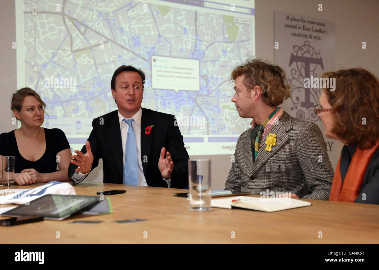 """El primer ministro David Cameron habla con los empleados durante una visita a la compañía de internet The Trampery en Shoreditch, Londres, después de que desafió a las empresas más pequeñas a salir de su """"zona de confort"""" y exportar bienes en el extranjero, ya que anunció que &Pound;95 millones se pondrá a disposición de la inversión. Foto de stock"""