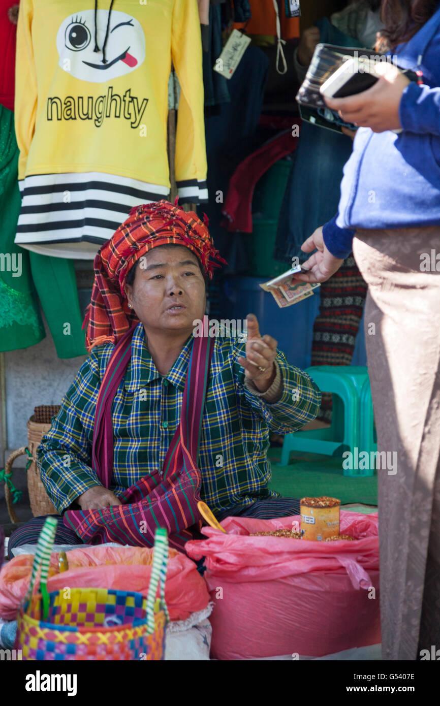 Una mujer vendedor de Pao Hill Tribe recibir el pago en efectivo en el mercado de Nyaungshwe (Myanmar). Vendeuse Imagen De Stock