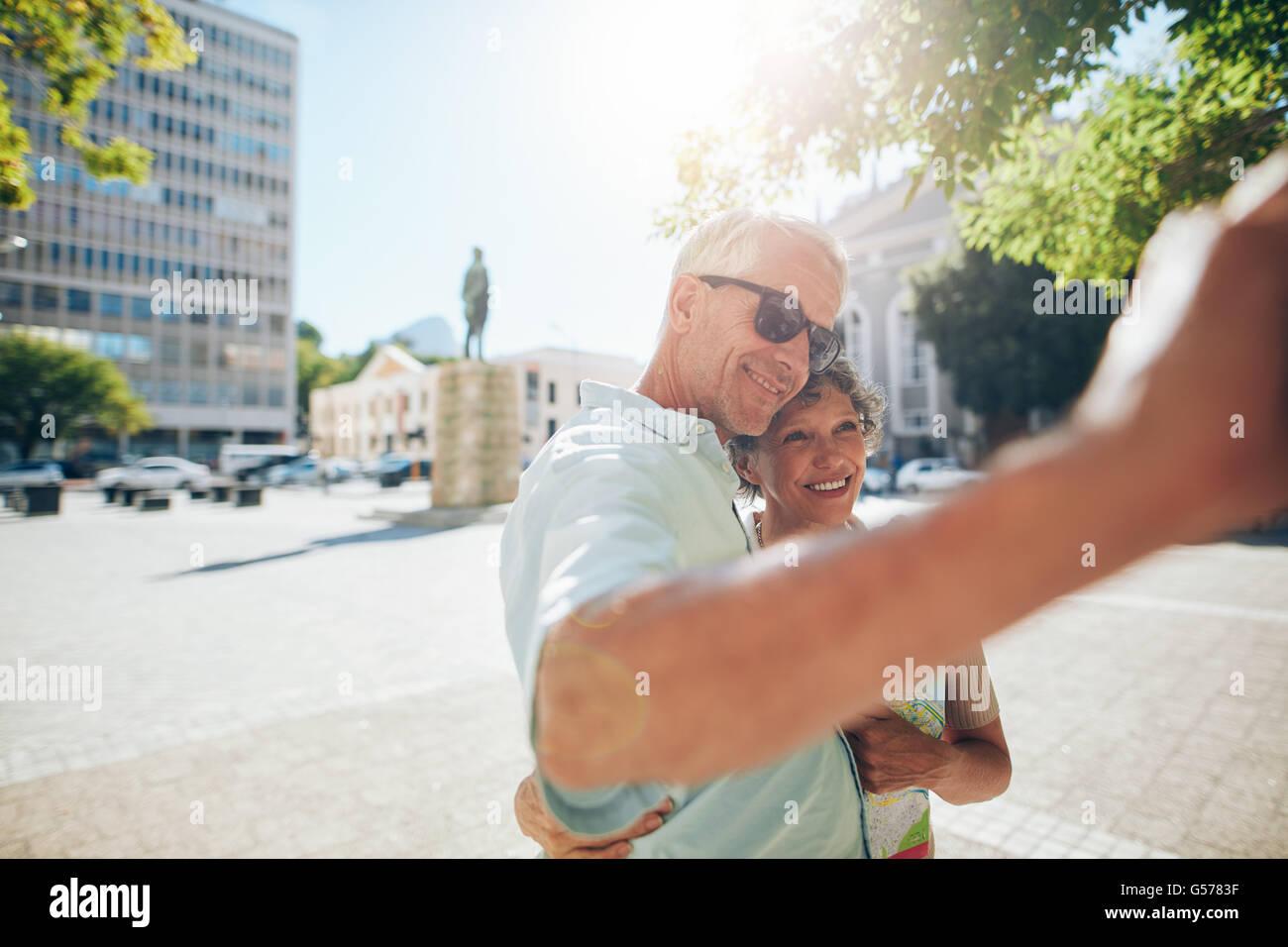 Feliz pareja senior y afectuoso abrazo y teniendo un selfie afuera. Turista tomar autorretratos en su verano vacat Imagen De Stock