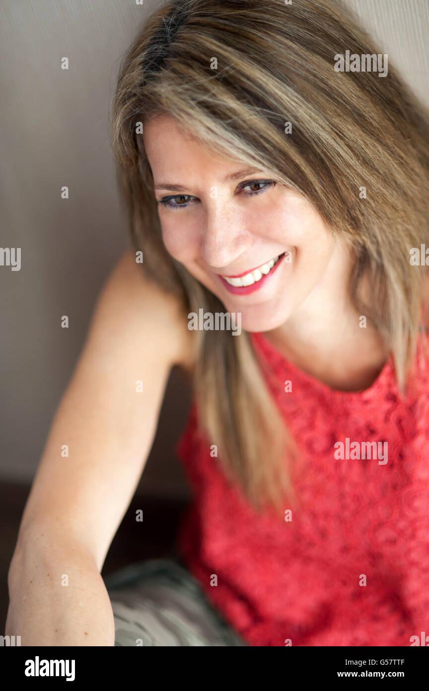 Cerca de 50 años rubia atractiva mujer mirando lejos de la cámara con gran sonrisa. Imagen De Stock