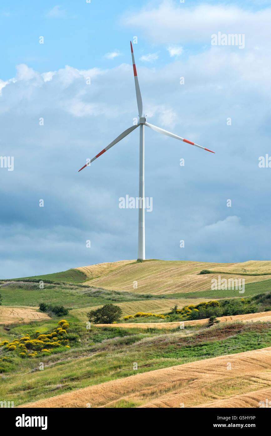 Aerogenerador en una colina rural contra un cielo nublado para la conversión de la energía cinética Imagen De Stock