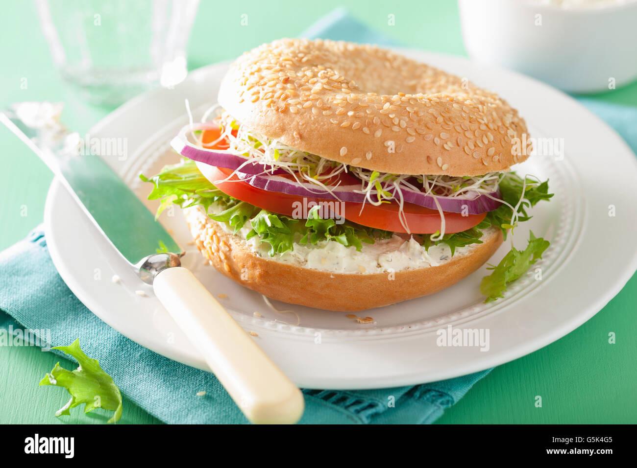 Sándwich de tomate en bagel con queso crema de lechuga cebolla brotes de alfalfa Foto de stock