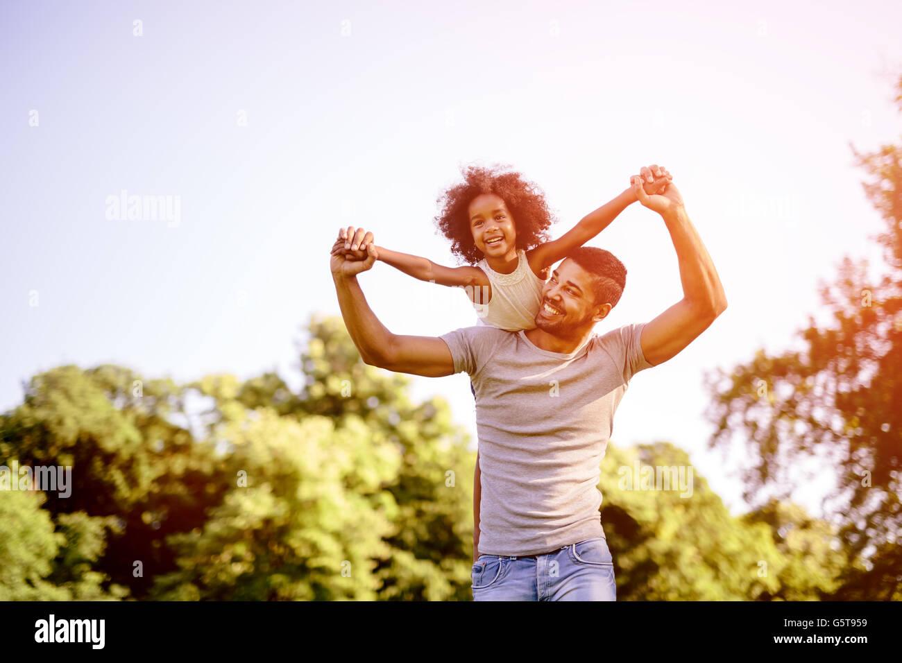 Niño volando sobre el padre hombros mientras permanecían piggyback Imagen De Stock
