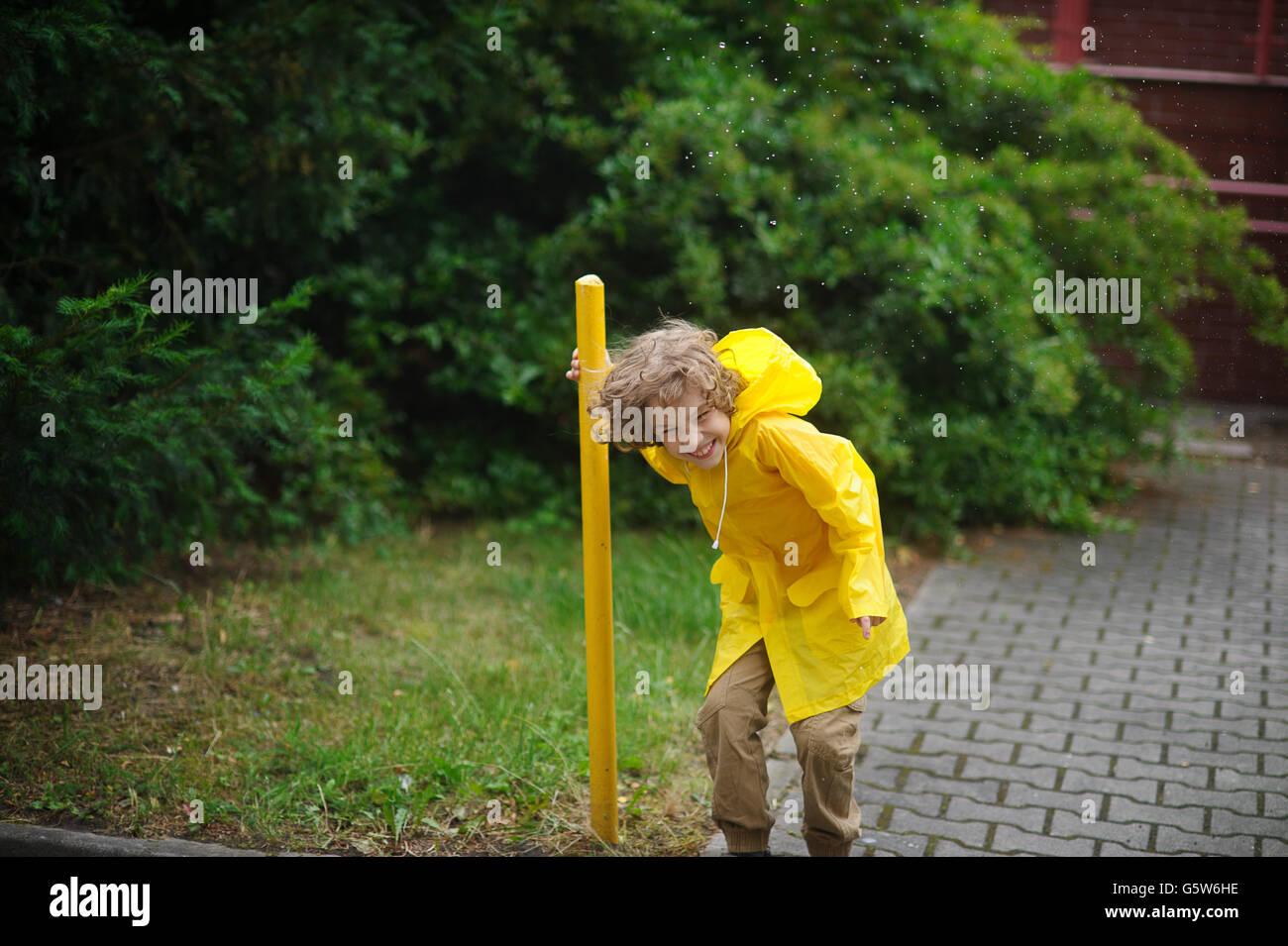 El chico en un impermeable amarillo está en la lluvia en el patio y se ríe  fuerte. Frías gotas de lluvia sobre la cabeza. El muchacho