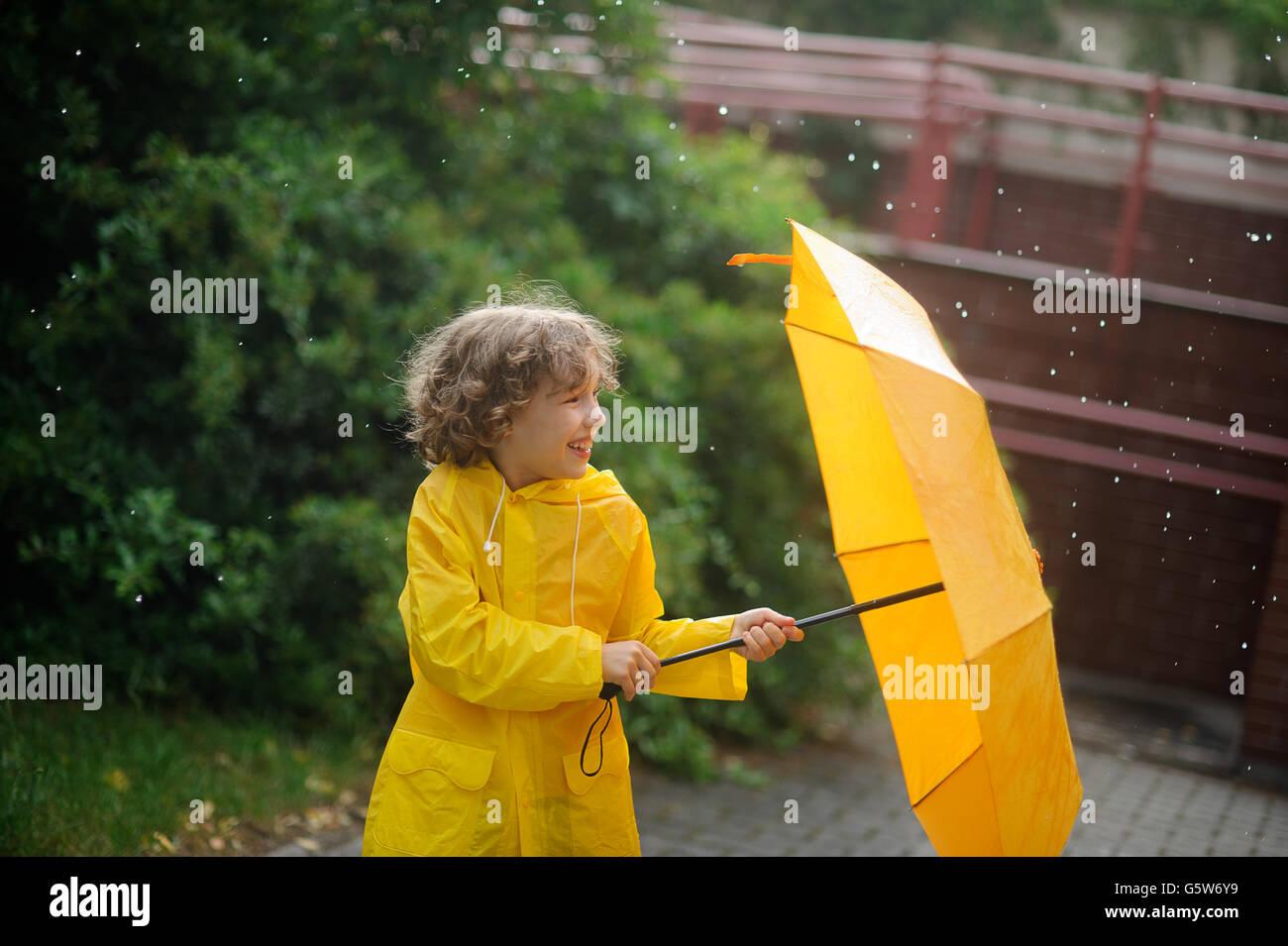 El chico en un impermeable amarillo brillante abre un paraguas bajo una  lluvia permanente. El niño está en el patio de la casa. Gotas de un r