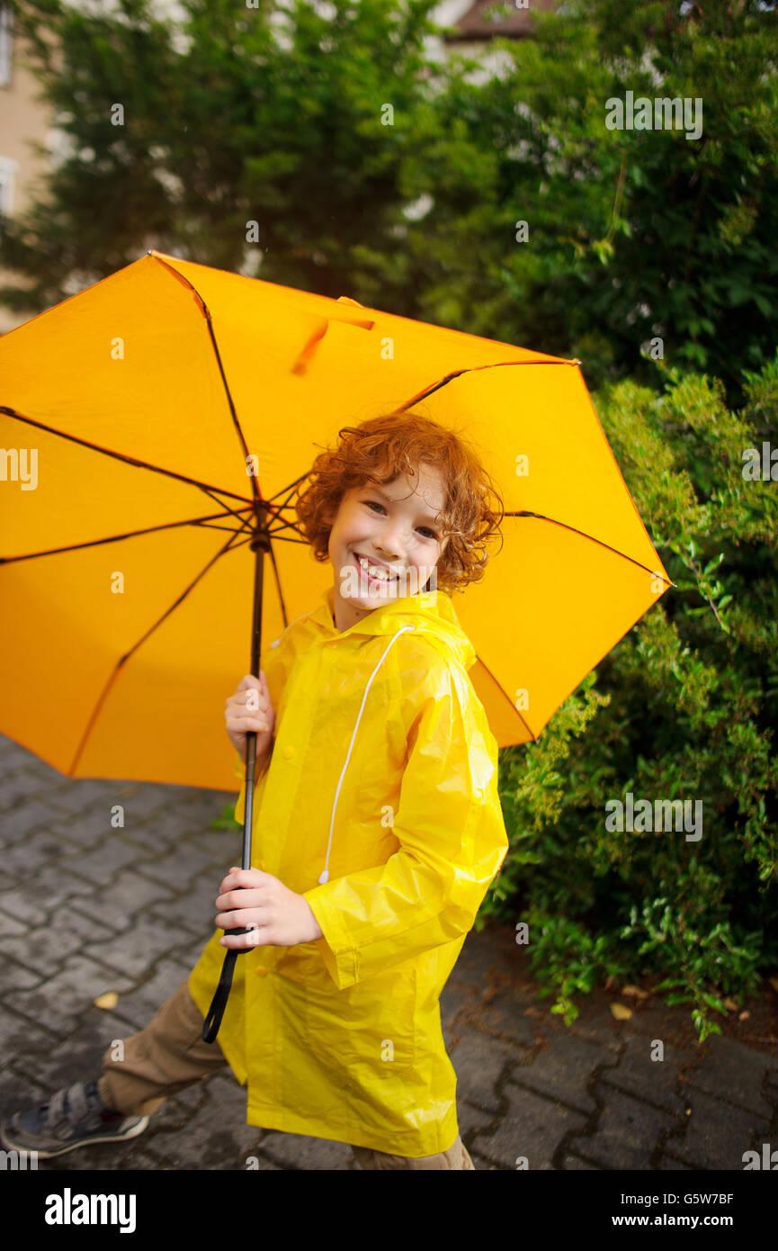 El chico lindo de 8-9 años bajo un paraguas amarillo. El chico en un  impermeable amarillo brillante posee un gran paraguas en mano. El niño l