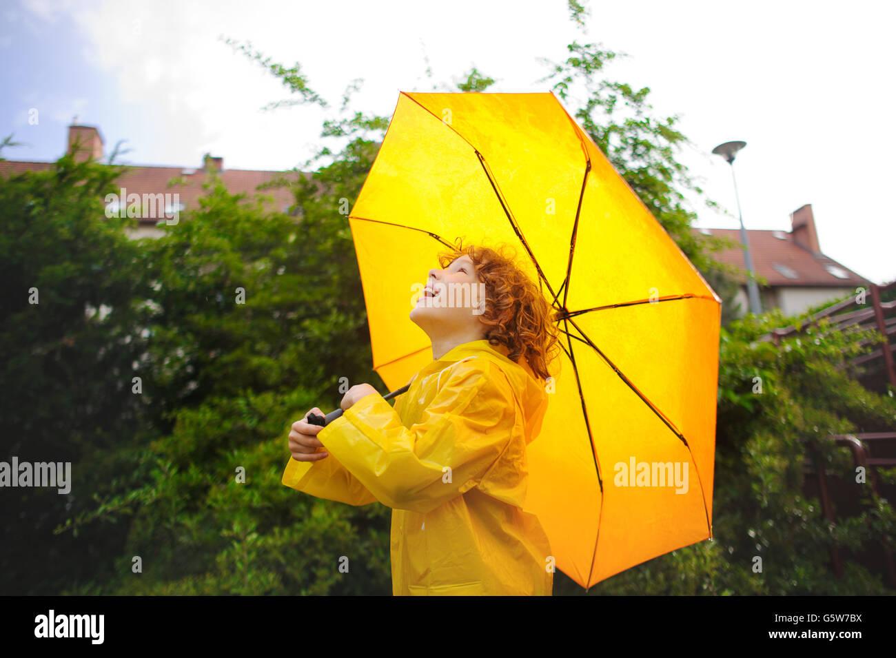 Niño alegre pararse bajo un paraguas amarillo en el patio de la casa. El  chico en un impermeable amarillo brillante. El niño se ve en