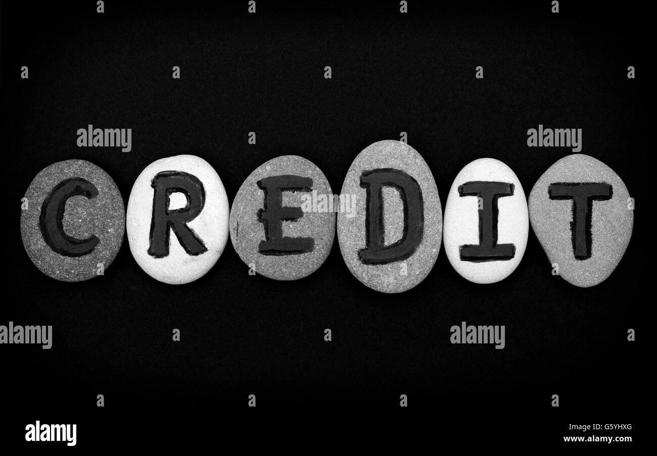Crédito Word deletrear desde piedras con letras sobre fondo negro. Cartas dibujadas por mí Imagen De Stock