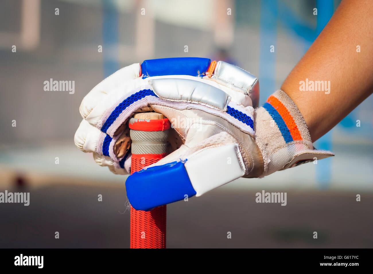 Niño sosteniendo caucásica bate de críquet & guante.aislados, el enfoque selectivo, profundidad Imagen De Stock