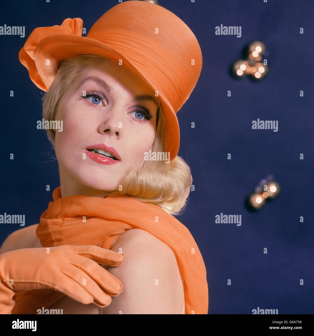 1960 moda mujer rubia de ojos azules modelo llevando un gorro de color naranja a juego con bufanda y guantes Imagen De Stock