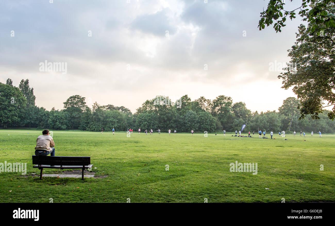 Hombre sentado en un banco en Wandsworth Common, Londres, Gran Bretaña. Imagen De Stock