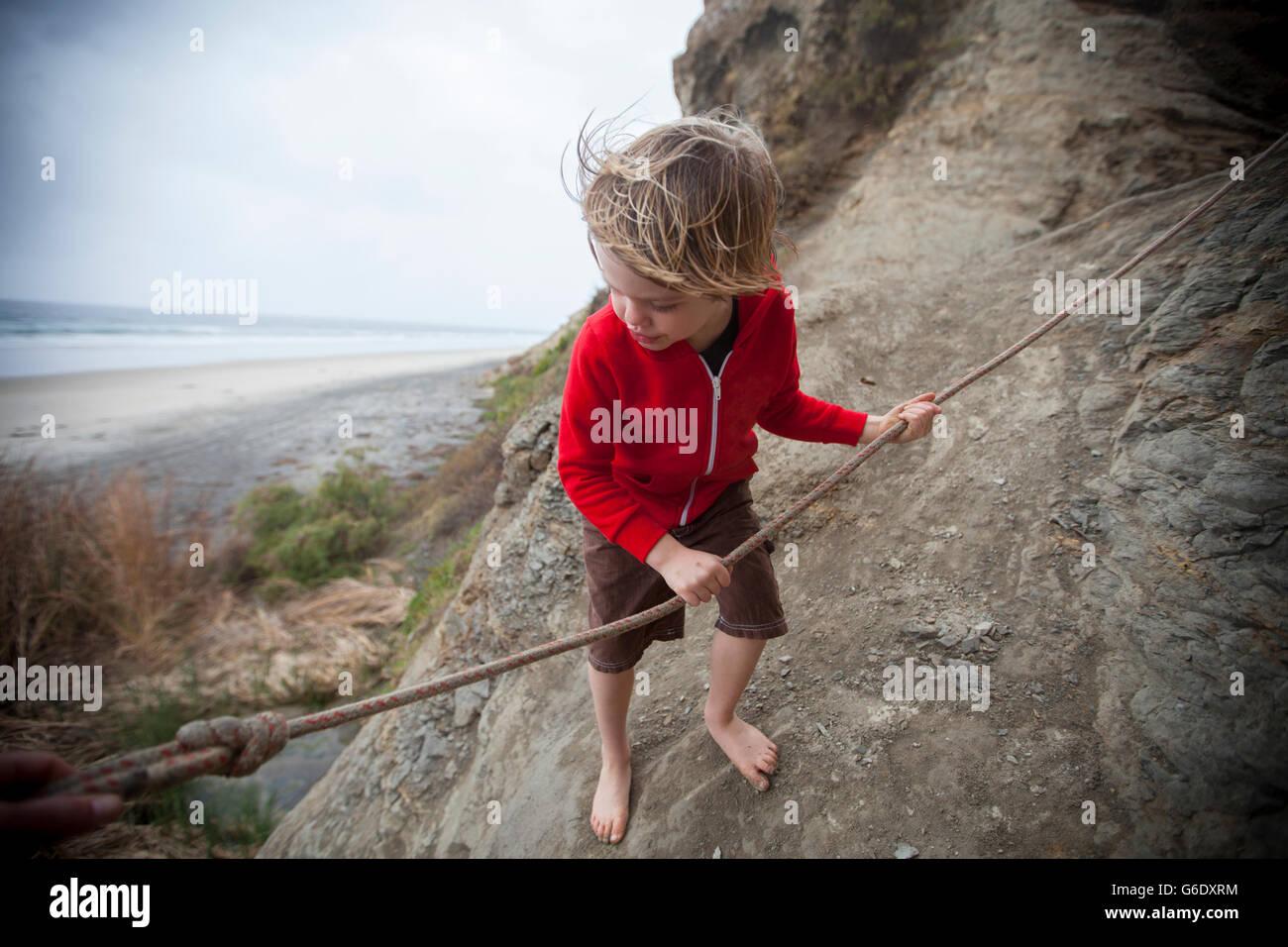 Niño de menos de 5 años de edad, usando la cuerda para bajar de la pared a Blacks Beach, La Jolla, California. Imagen De Stock