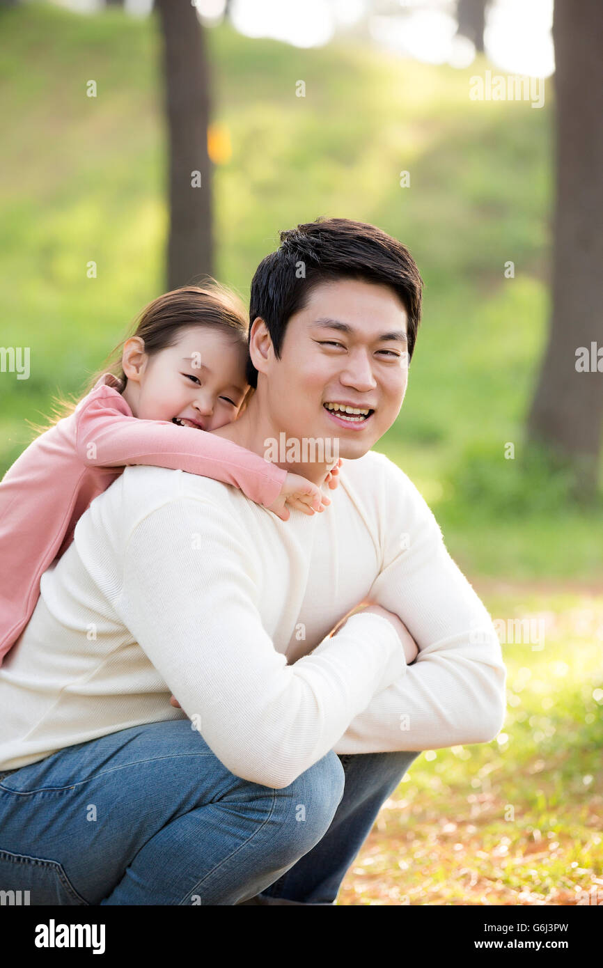 El padre y la hija de Asia feliz y sonriente posando en el bosque Imagen De Stock