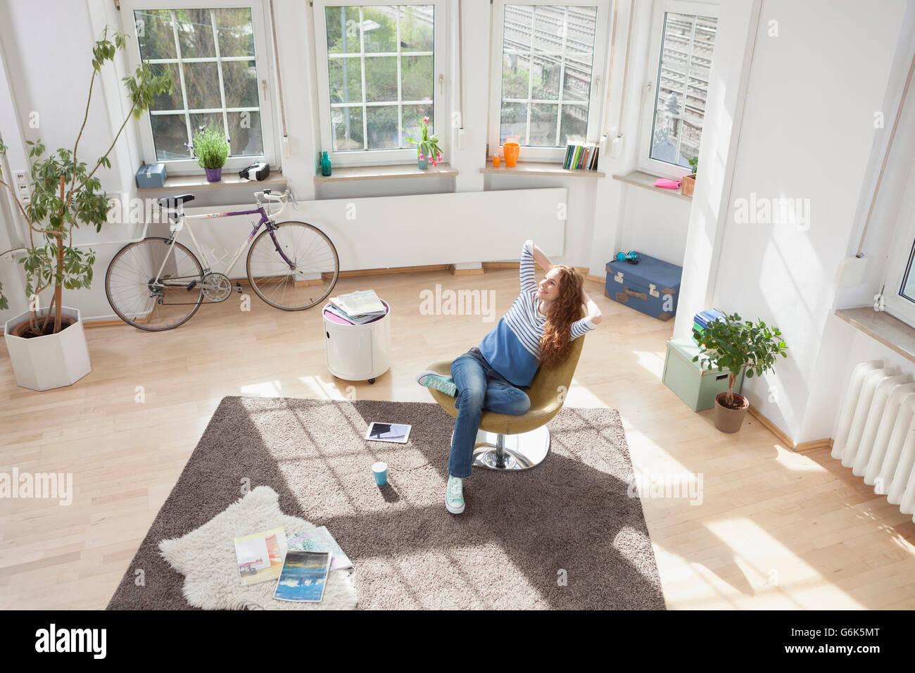 Mujer relajado en casa, sentado en la silla Imagen De Stock