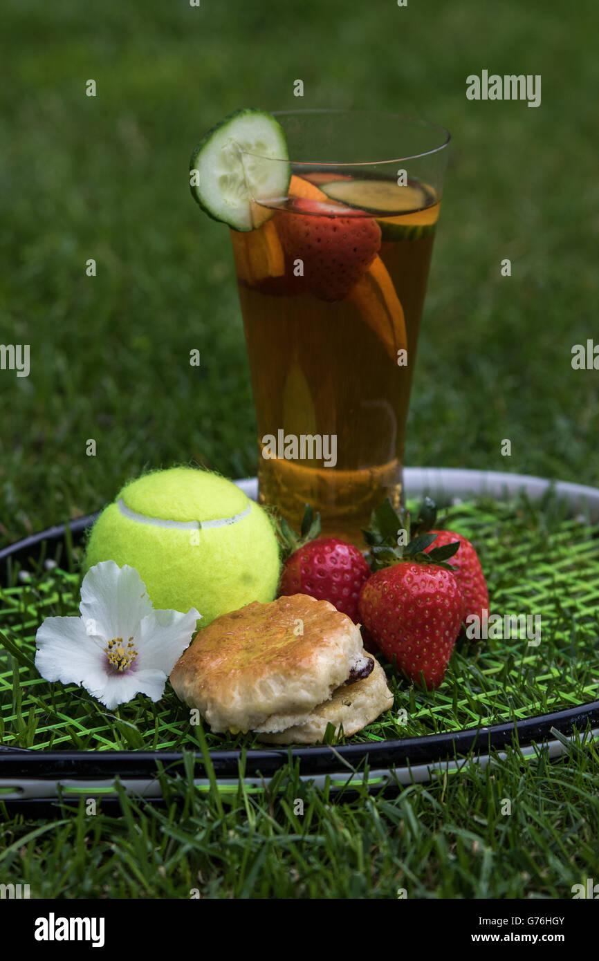 Picnic de verano establecidos en una raqueta de tenis sobre hierba con flor Foto de stock