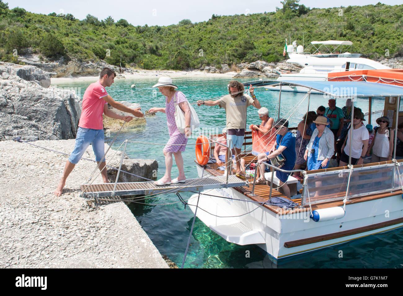 Ancianos pasajera ayudado off barco de cruceros turísticos en la diminuta isla de AntiPaxos, Grecia en un viaje Imagen De Stock