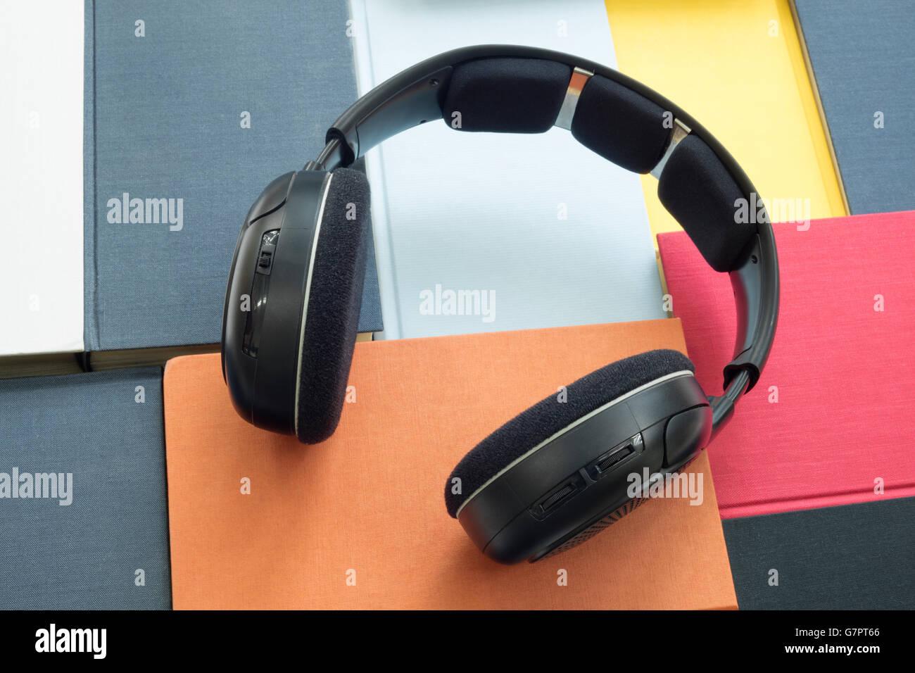 Grupo de coloridos auriculares y libros relacionados con audiolibros, e-books y escuchar conversaciones digitalmente Foto de stock