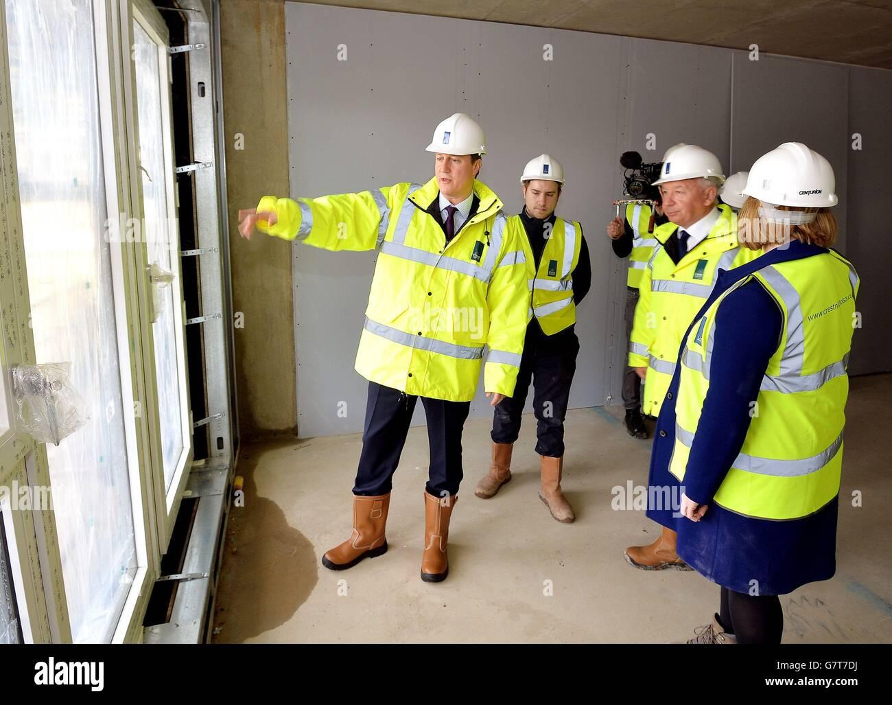 El primer ministro David Cameron ve el trabajo de construcción casi terminado con el CEO de CREST Building Steve Stone (tercera izquierda), durante una visita a un sitio de construcción donde están construyendo pisos privados en Isleworth, al oeste de Londres. Foto de stock