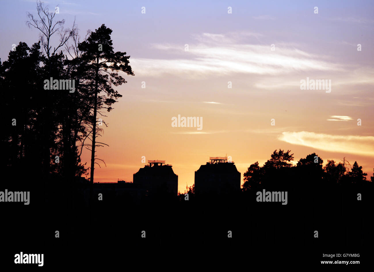 Naranja atardecer y dos casas con contornos de árboles Imagen De Stock