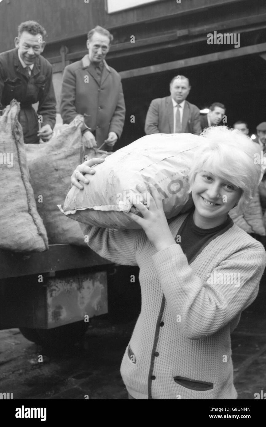 """Sandra Sherlock, de 17 años, de Elsworth Street, Leeds, hace un trabajo ligero de una bolsa de combustible que abultaba durante su trabajo como """"hombre de carbón"""" en el negocio de su familia. Ella dijo: """"Lo he estado haciendo desde que salí de la escuela. Mi madre conduce el camión y yo ayudo a entregar el carbón, el coque y los ladrillos de carbón. Me gusta la vida, y llevar sacos de carbón no significa nada para mí. A menudo estoy arriba y apagado en las rondas a las cinco de la mañana. Foto de stock"""