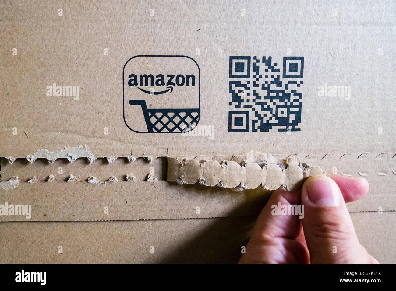 El cliente abre un paquete recibido de cartón de Amazon.com tienda online Imagen De Stock