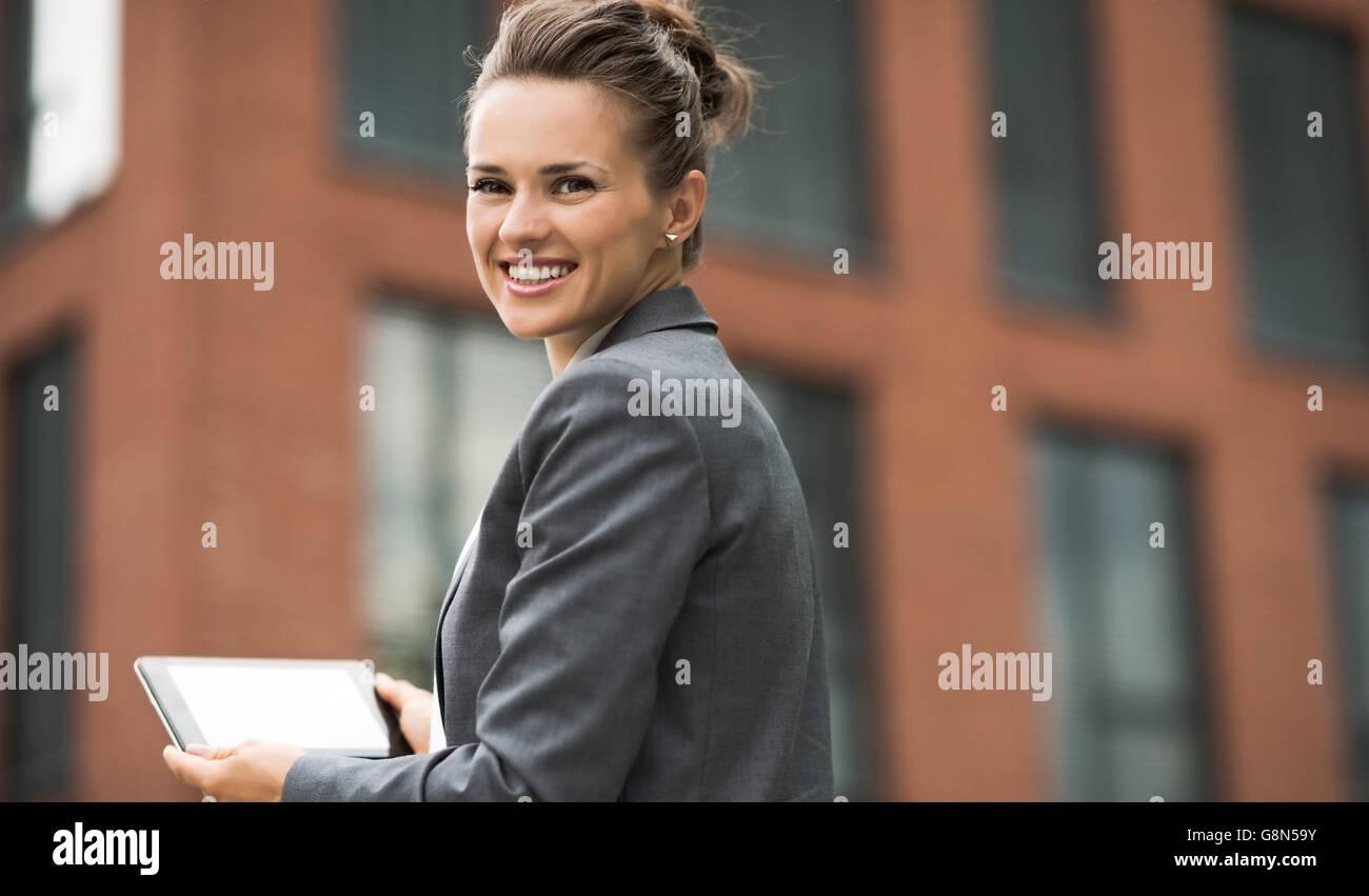 El nuevo negocio. Sonriente mujer de negocios moderno contra el edificio de oficinas con Tablet PC Foto de stock